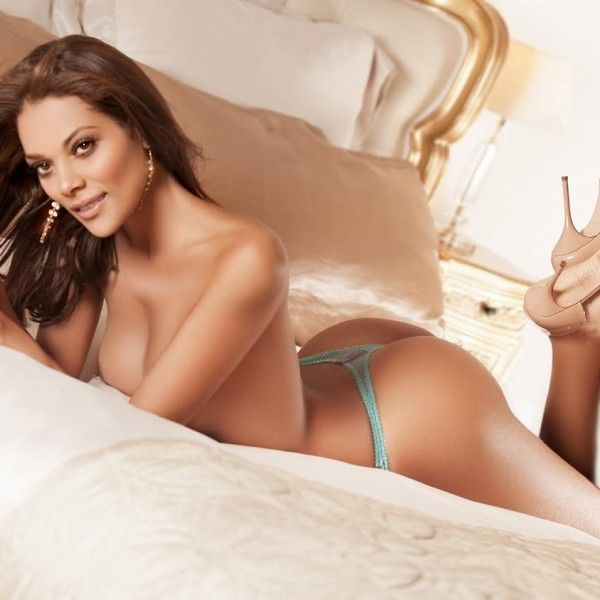 Nude woman lying on a bed in a thong and high heels