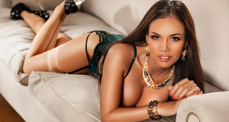 Woman in make up high heels and lingerie seductively laid across a couch